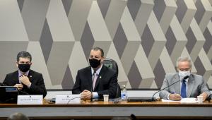 Três homens brancos sentados em uma mesa um ao lado do outro com placas com seus nomes à frente. Usam terno, o da esquerda e meio terno preto e o da direita cinza
