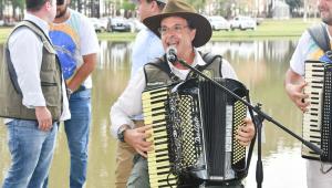 Sentado à frente de um microfone, usando chapéu, óculos,, colete e calça, o ministro Gilson Machado toca sanfona e canta a céu aberto, com outro sanfoneiro à sua esquerda; atrás dele, três pessoas conversam