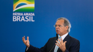 Em trajes sociais, mas sem gravata, Paulo Guedes abre os braços enquanto fala; atrás dele, uma parede azul com a bandeira do país estilizada e a frase Pátria Amada Brasil