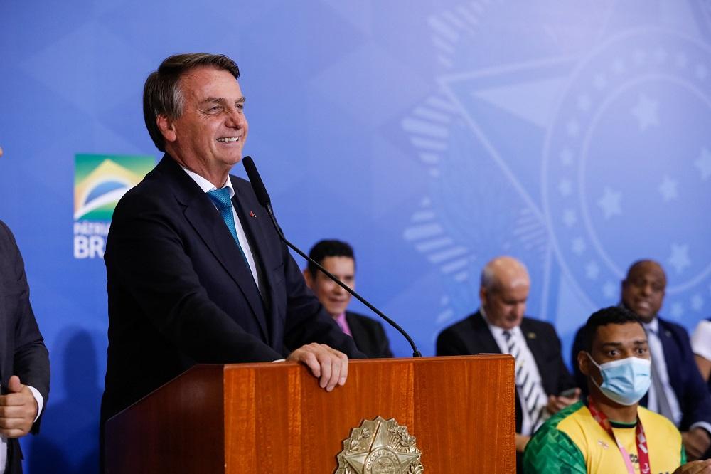 Diante de um púlpito no Palácio do Planalto, o presidente Jair Bolsonaro discursa na cerimônia de recepção aos atletas olímpicos e paralímpicos; alguns de seus ministros aparecem atrás, sentados, um pouco desfocados