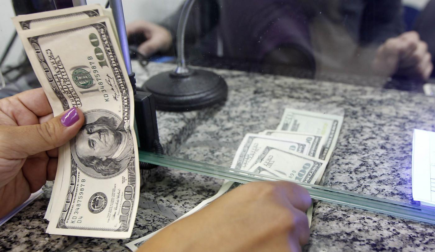 Mulher conta notas de dólar no guichê da casa de câmbio