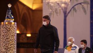 De máscara, calça jeans e jaqueta, Jair Bolsonaro caminha pelo Santuário de Aparecida e observa a imagem de Nossa Senhora, que está em um altar