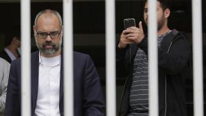O jornalista Allan dos Santos à frente de um portão, que, devido ao enquadramento da foto, faz parecer que ele está atrás das grades