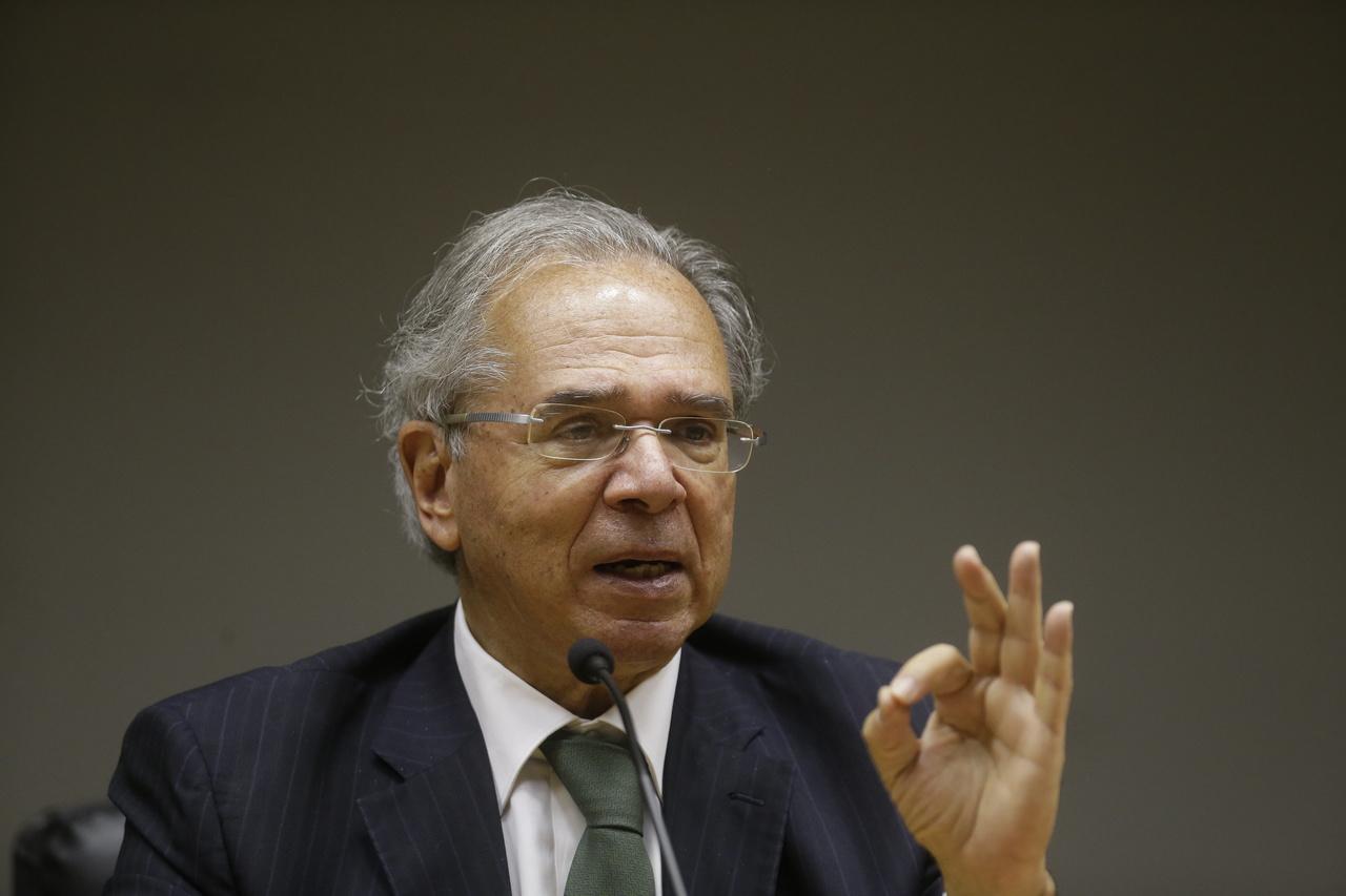 Ministro da Economia, Paulo Gedes fala com a mão levantada