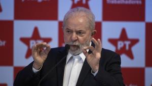 Presidente Lula unindo os dois polegares aos indicadores e falando em um microfone. Usa terno e camisa branca. Atrás, logos do PT