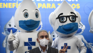 Marcelo Queiroga, homem com cabelos grisalhos e máscara branca, fala ao microfone sentado em uma mesa. Atrás, dois mascotes Zé-Gotinha com máscaras azuis. Eles tem a forma de uma gota e são brancos, com símbolos do SUS no peito, e um usa óculos de grau