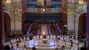 Imagem de uma igreja em Aparecida com uma espécie de elevado redondo e vários padres sentados em cadeira em uma roda. No meio, um altar. Atrás, há duas fileiras com várias pessoas sentadas em bancos de igreja.