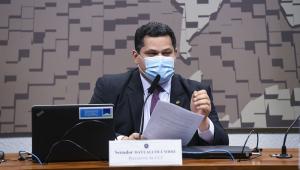 O senador Davi Alcolumbre, de terno azul marinho,, camisa azul clara, gravata azul com quadradinhos brancos e máscara branca, sentado à sua mesa de presidente da CCCJ (com letreiro que indica o cargo)