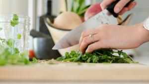Mão com uma faca corta salada em uma tábua na cozinha