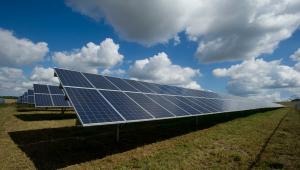 Painéis de energia solar em destaque num gramado sob o céu azul com algumas nuvens