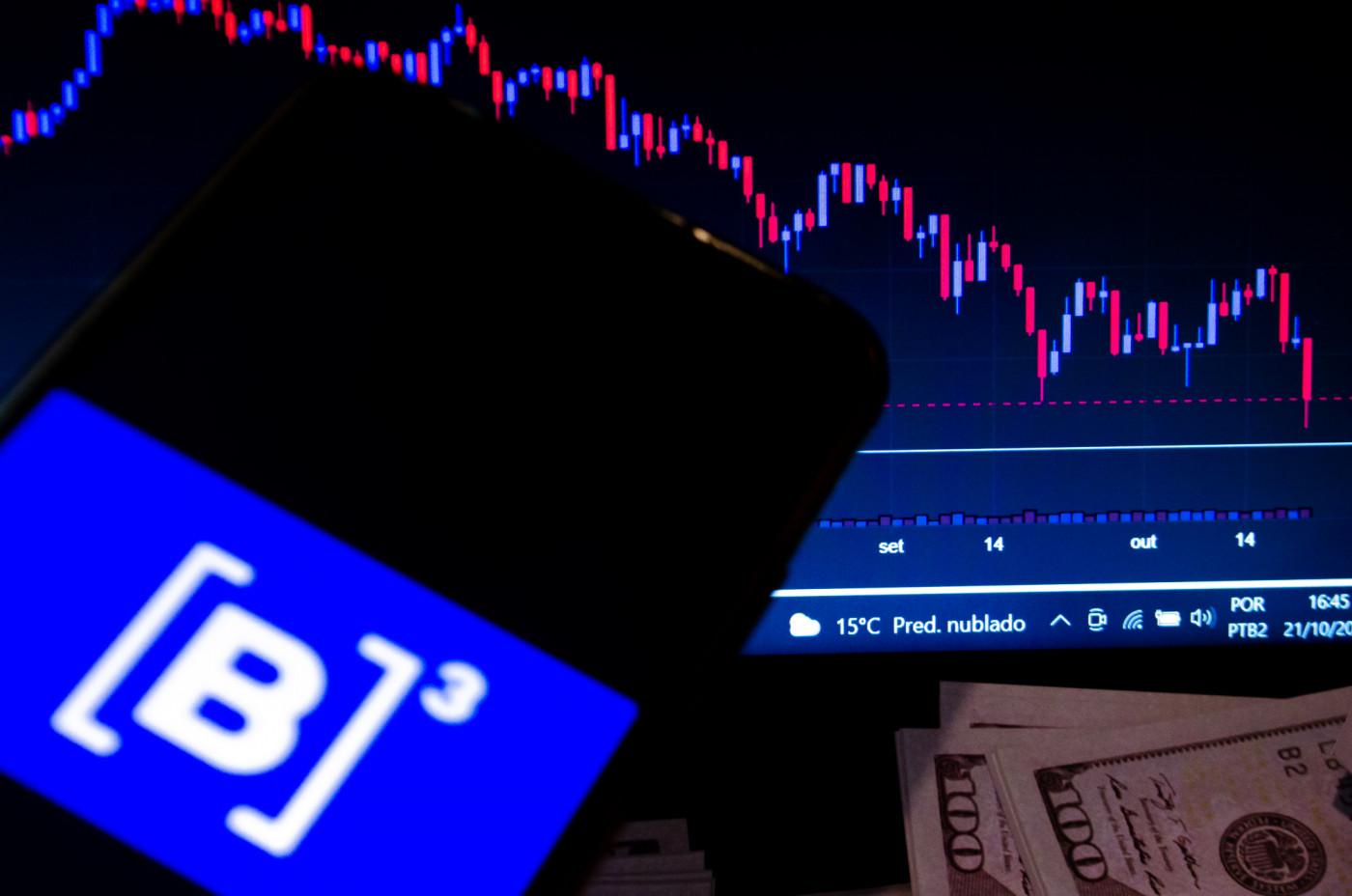 Celular com o logo da B3 na frente de um gráfico com a movimentação da Bolsa de Valores