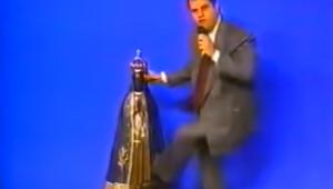 Imagem de um bispo, em frente a um fundo azul, vestido com trajes sociais, acertando o pé em uma imagem de Nossa Senhora de Aparecida