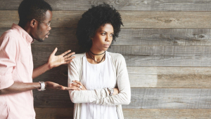 Enquanto um homem gesticula e tenta se desculpar, a mulher olha para o outro lado com cara emburrada; ambos são jovens e negros