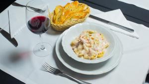 Prato de Penne com milho branco e vegetais, colocado à mesa com um copo de vinho e uma porção de torradas