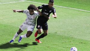 Willian, do Corinthians, e Fabrício Bruno, do Bragantino, disputam a bola em partida de futebol