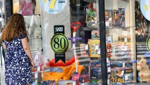 Mulher de vestido observa vitrine de loja de brinquedos em rua do centro de Campinas