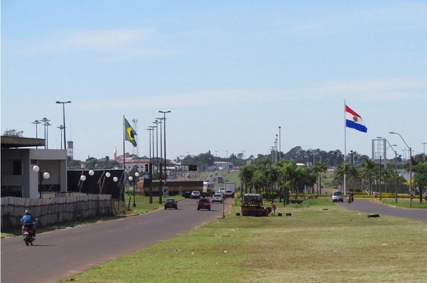 Fronteira entre Brasil e Paraguai, com duas ruas dividas por um canteiro central, com a bandeira de cada país em sua respectiva via
