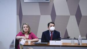 Homem de terno e máscara ouve pergunta de senador