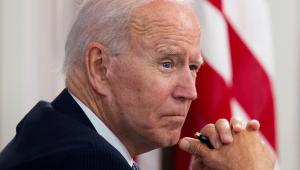 Joe Biden apoia a mão no queixo de perfil