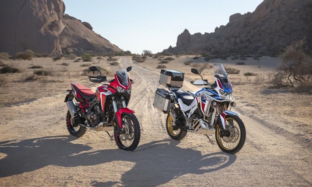 Duas motocicletas lado a lado, uma predominantemente vermelha, à esquerda, e a outra azul, em uma estrada de terra com montanhas rochosas compondo a paisagem