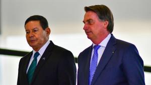 Vestidos em trajes socais, Hamilton Mourão (à esquerda) e Bolsonaro caminham lado a lado no Palácio do Planalto