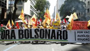 Pessoas umas ao lado das outras segurando um cartaz escrito 'Fora Bolsonaro'. Elas marcham em uma rua, usam camisetas amarelas e levam bandeiras e cartazes vermelhos e amarelos