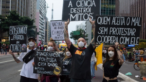 Cinco jovens manifestantes (dois homens e três mulheres), todos de preto, levantam cartazes contra Bolsonaro na Avenida Paulista