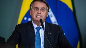 O presidente Jair Bolsonaro falando em microfone com uma bandeira do Brasil ao fundo