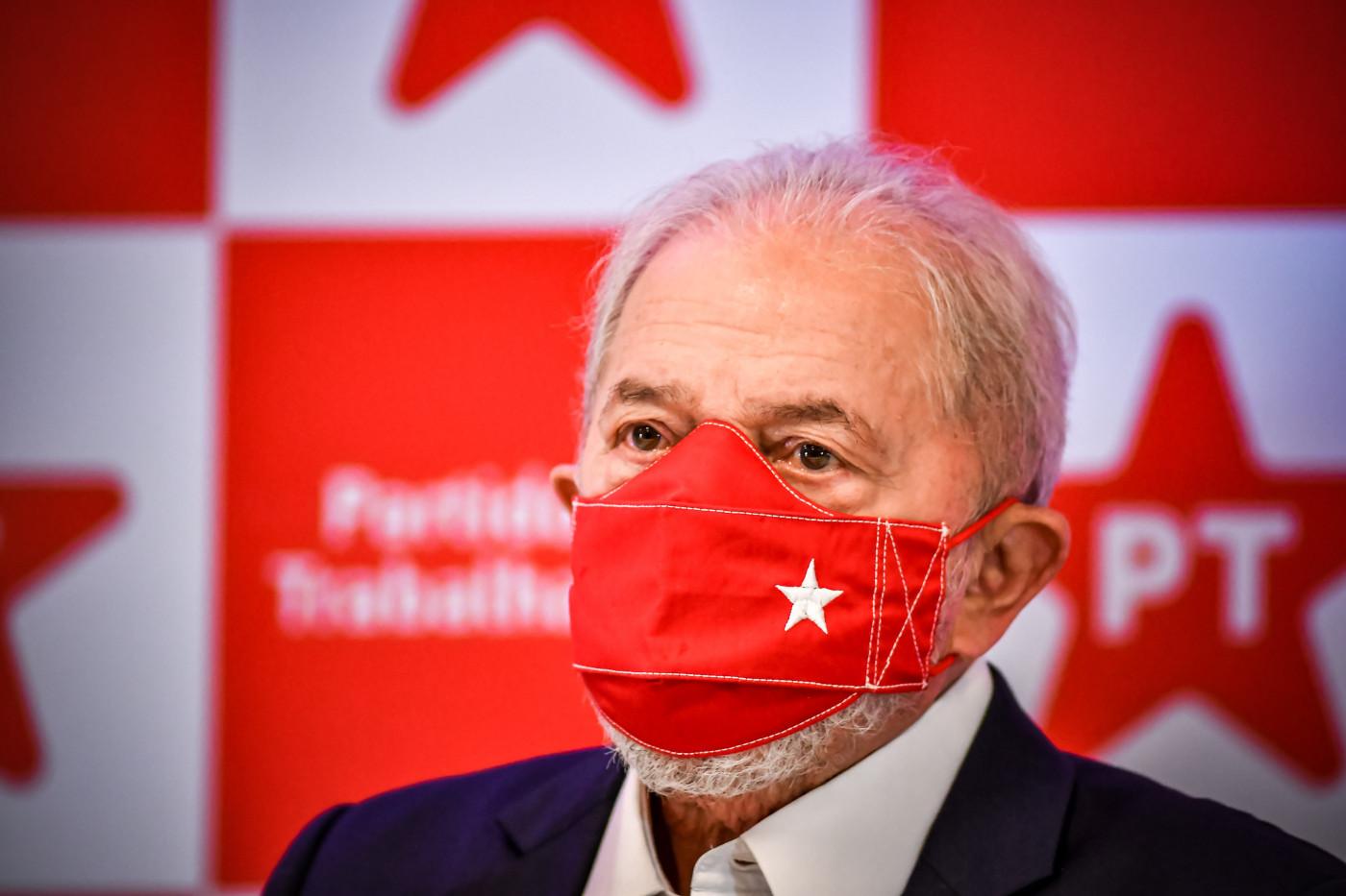 Ex-presidente Lula olhando para o horizonte com uma máscara de proteção vermelha com uma estrela branca. Atrás, logos do PT