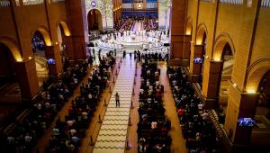 Foto tirada do alto e quatro fileiras com várias pessoas sentadas em cadeiras em uma igreja. No meio, há um caminho branco.