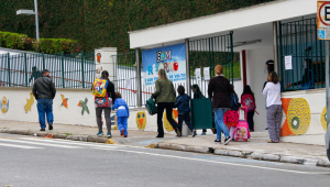 Pais e alunos em frente a uam escola