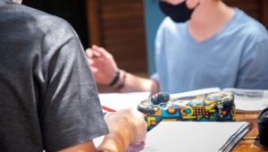 Um aluno de costas, de camisa cinza, lápis na mão direita e o caderno ao lado, e outro de camiseta azul clara e máscara preta, do outro lado da mesa