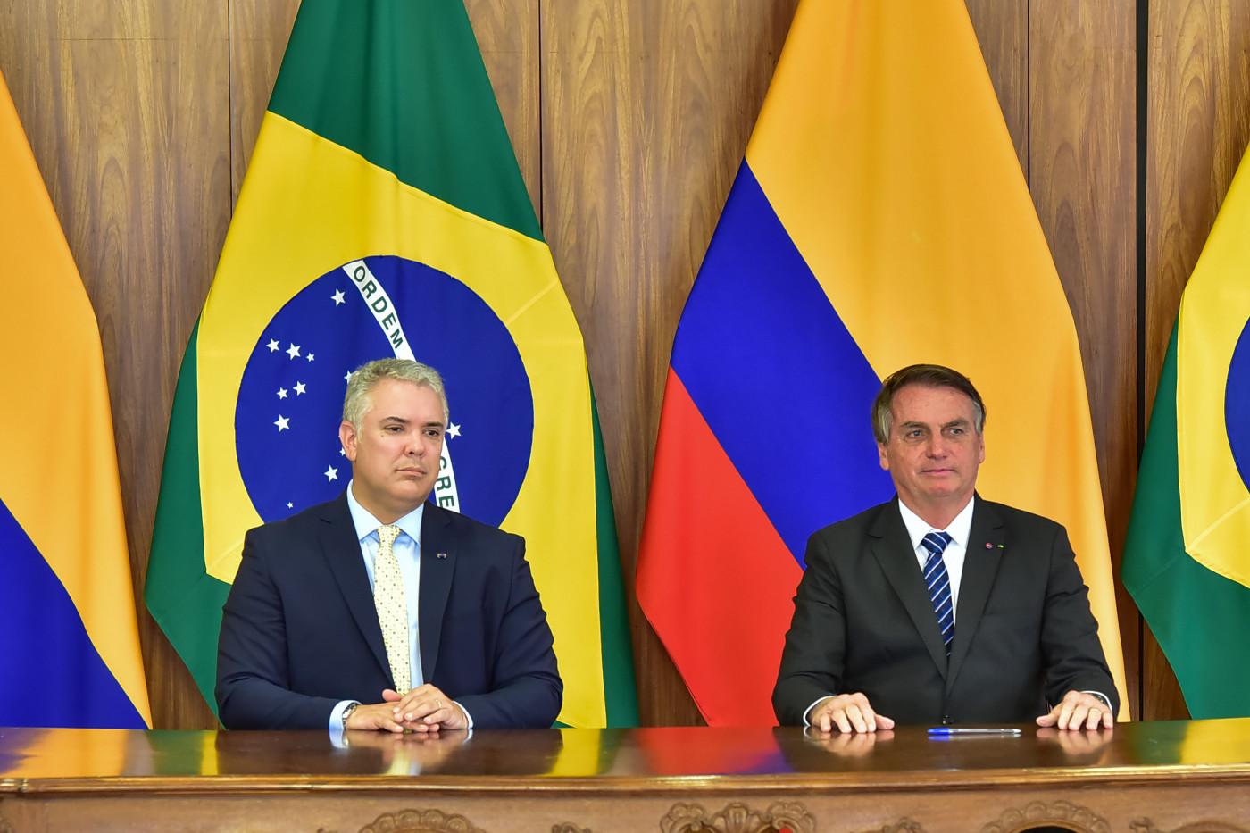 O presidente Ivan Duque, da Colômbia, e presidente Jair Bolsonaro sentados em uma bancada em frente às bandeiras dos países