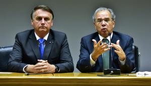 Jair Bolsonaro e Paulo Guedes lado a lado, sentados à frente de uma mes