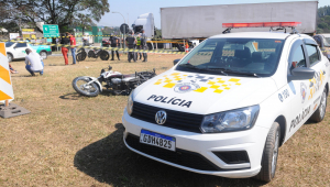 Carro da polícia militar ao lado de moto caída