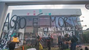 """Uma casa, sede de associação agropecuária, é ocupada por manifestantes antigovernistas, pichada na fachada com a frase """"Bolsonaro é morte"""" e decorada com faixas contra o presidente e o agronegócio"""