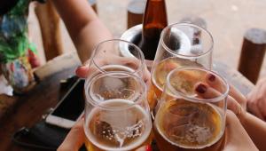 Imagem de um brinde com quatro copos de cerveja, em que a garrafa, com um isolante térmico, aparece sobre a mesa