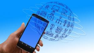 Mão segura um smartphone em um cenário com ym globo e diversos ícones que indicam prosperidade, lazer, finanças e estabilidade econômica