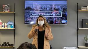 """Fernanda Torres, mulher na faixa dos 40 anos, dá uma palestra em uma sala com prateleiras dos dois lados e um monitor de TV atrás dela, posicionado pouco acima da cabeça, com """"Favela de Paraisópolis"""" escrito na tela (com a comunidade ao fundo)"""