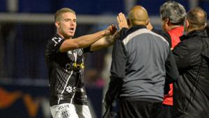 Jogador da Ponte Preta comemorando um gol e dois homens de costas para a câmera e de frente para ele