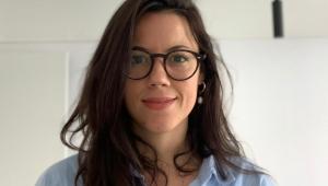 Mulher sorrindo de boca fechada para a câmera com óculos de grau preto, cabelos castanhos longos e meio ondulados. Usa uma camisa azul.