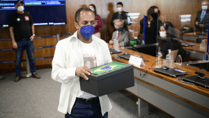 Homem de camisa carrega caixa com lenços