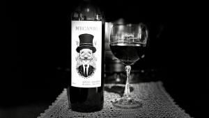 Foto em preto e branco de uma vinho com rótulo de um homem usando chapéu e uma taça servida pela metade ao lado