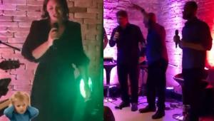 Michelle Bolsonaro cantando no karaokê, segurando um microfone e usando um vestido de manga 3/4 preto; três homens cantando no karaokê com calças e camisas pretas e segurando microfones