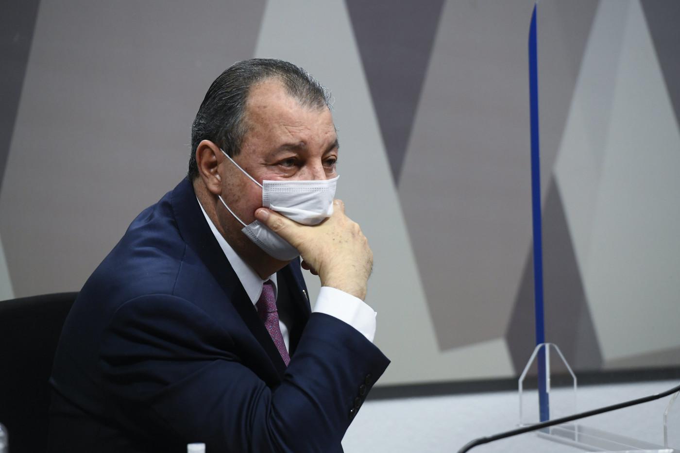 Omar Aziz apoia a mão no rosto, usando máscara de proteção branca