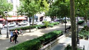 Rua com duas calçadas, sendo uma elas bem ampla, com bancos, alguns transeuntes, jardins e diversas árvores