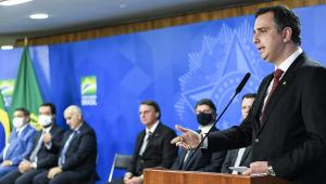 Enquanto Rodrigo Pacheco fala em um púlpito no canto direito da imagem, Jair Bolsonaro, Luiz Fux e alguns ministros e assessores do presidente da República observam sentados ao fundo