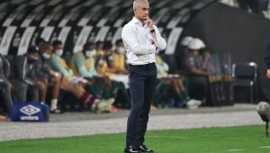 Sylvinho com camisa branca e calça jeans com a mão no queixo durante jogo do Corinthians