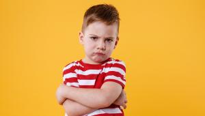 Vestido com uma camisa com listras verticais vermelhas e brancas, em frente a um fundo laranja, menino loiro de mais ou menos 3 anos enruga o queixo e olha para a câmera fazendo manha