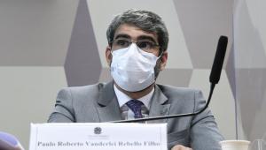 Homem de máscara ouve questionamento de senador